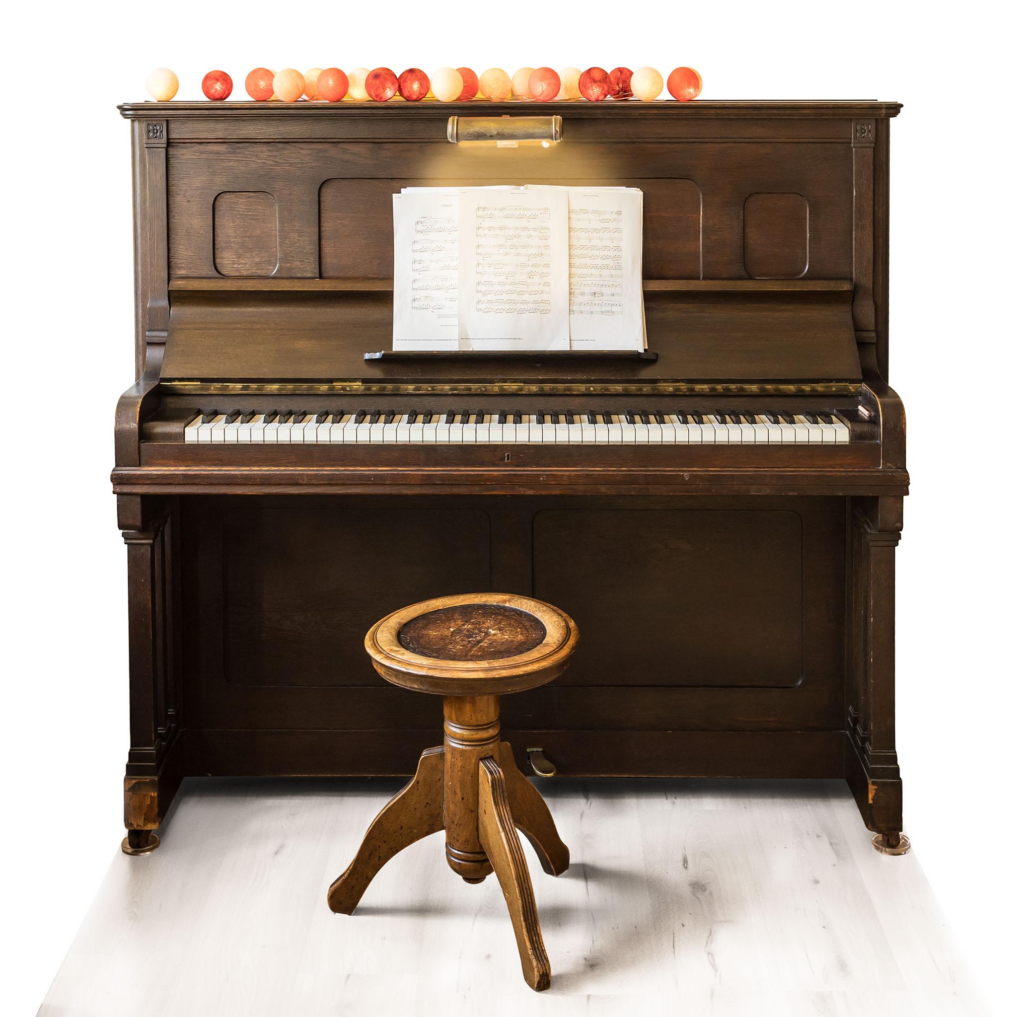 Altes Klavier aus dunklem Holz, davor ein Dreibeinhocker