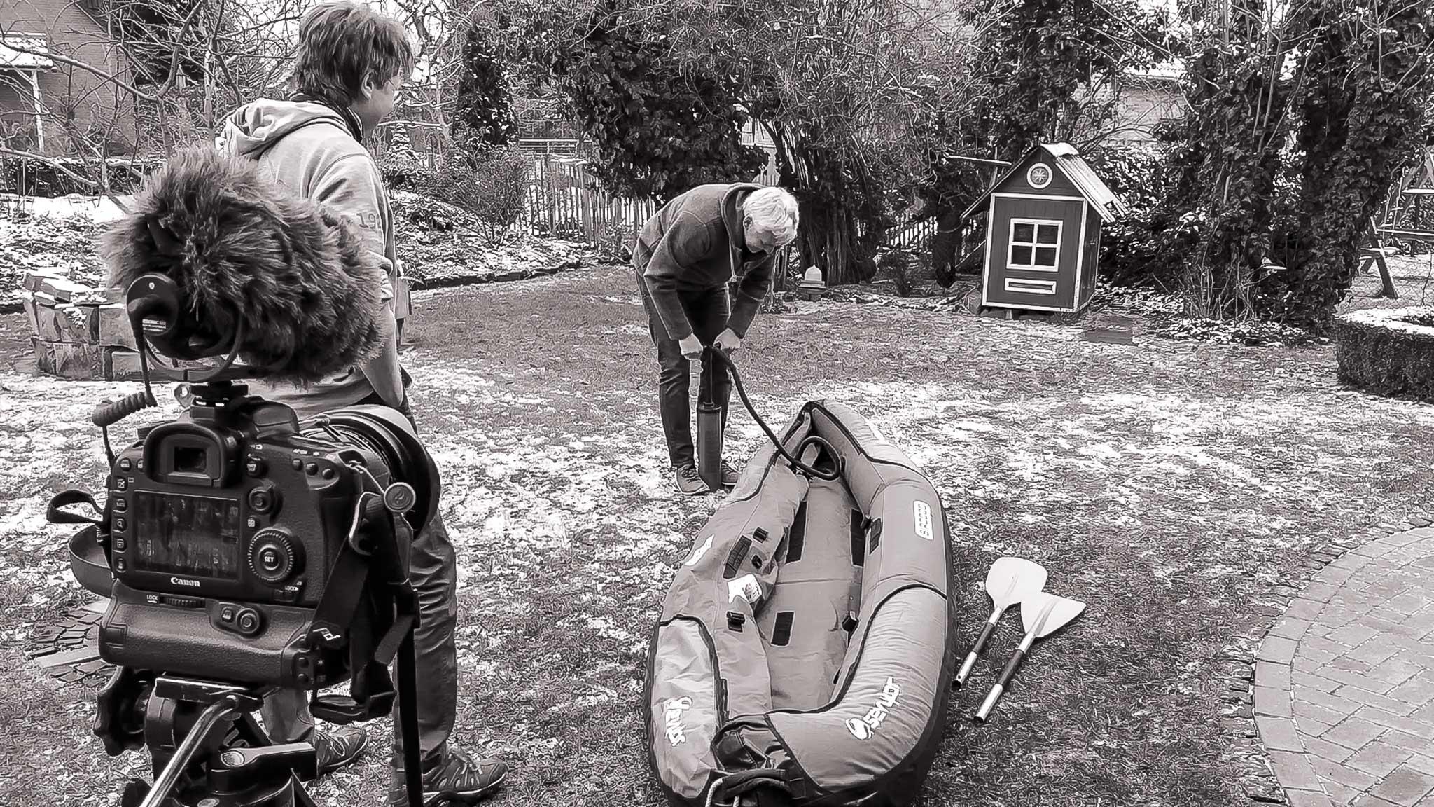 Michael pumpt im Garten das Boot auf