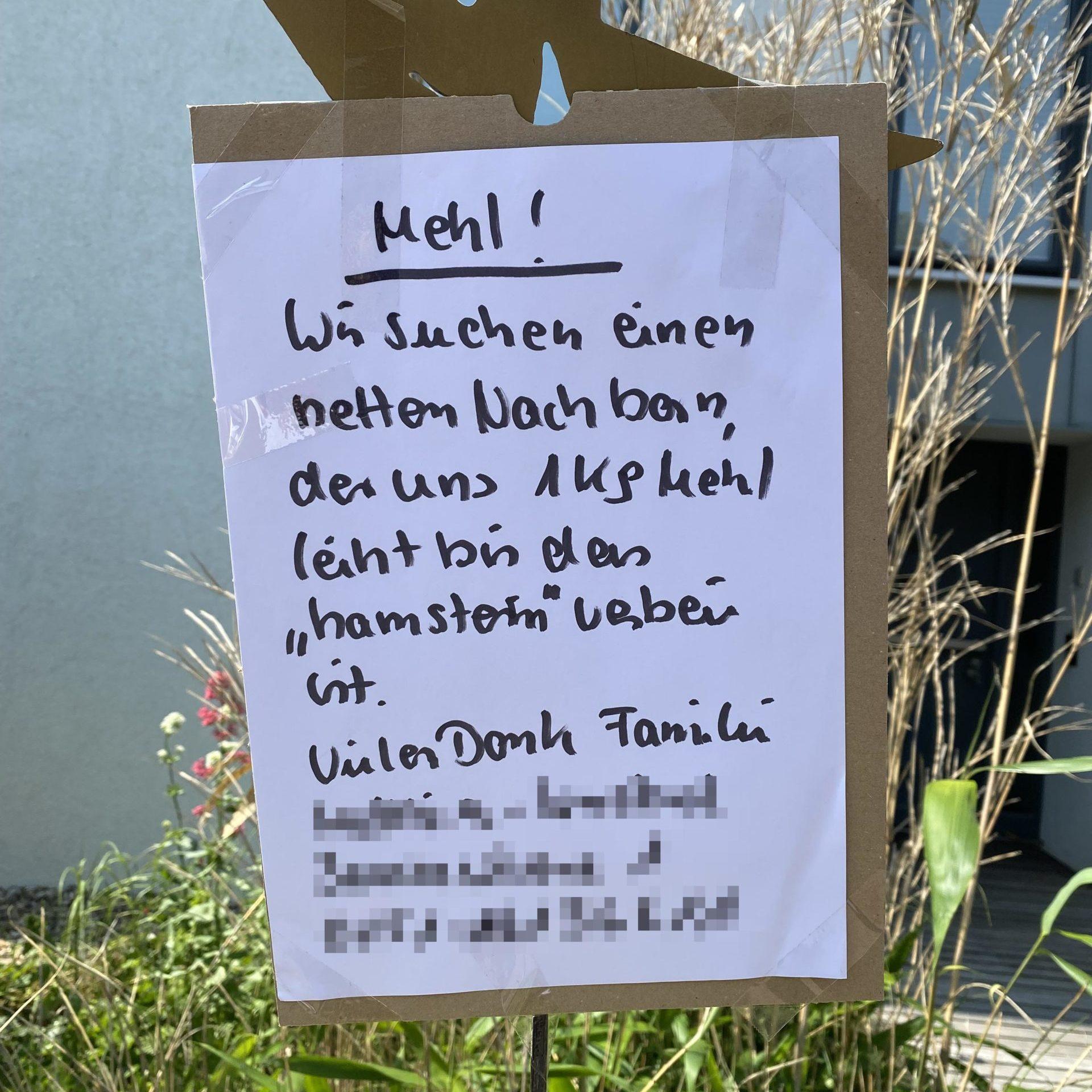 Schild mit Text: Wir suchen Nachbarn, der uns Mehl leiht.