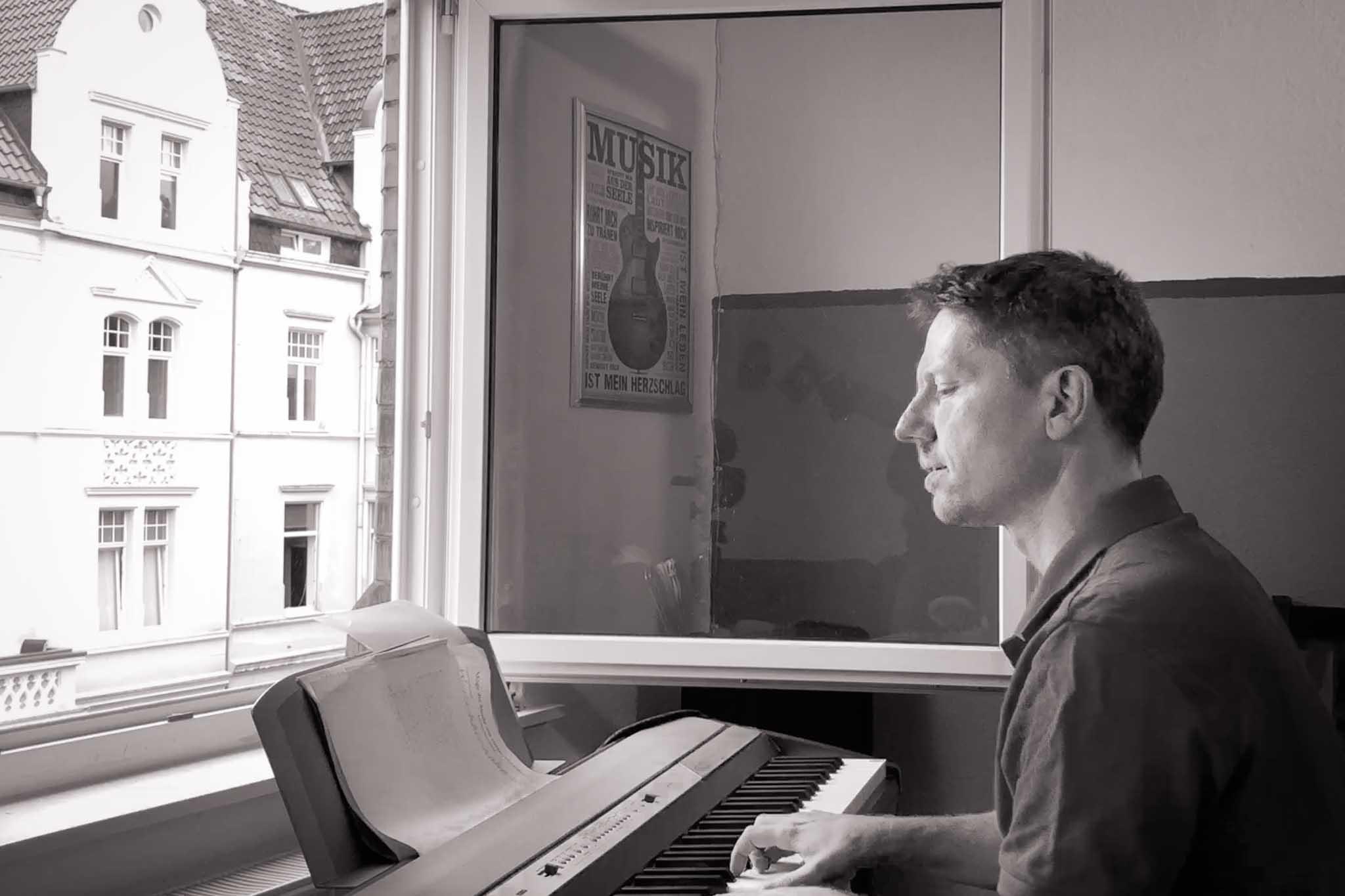 Matthias am Keyboard vorm offenen Fenster