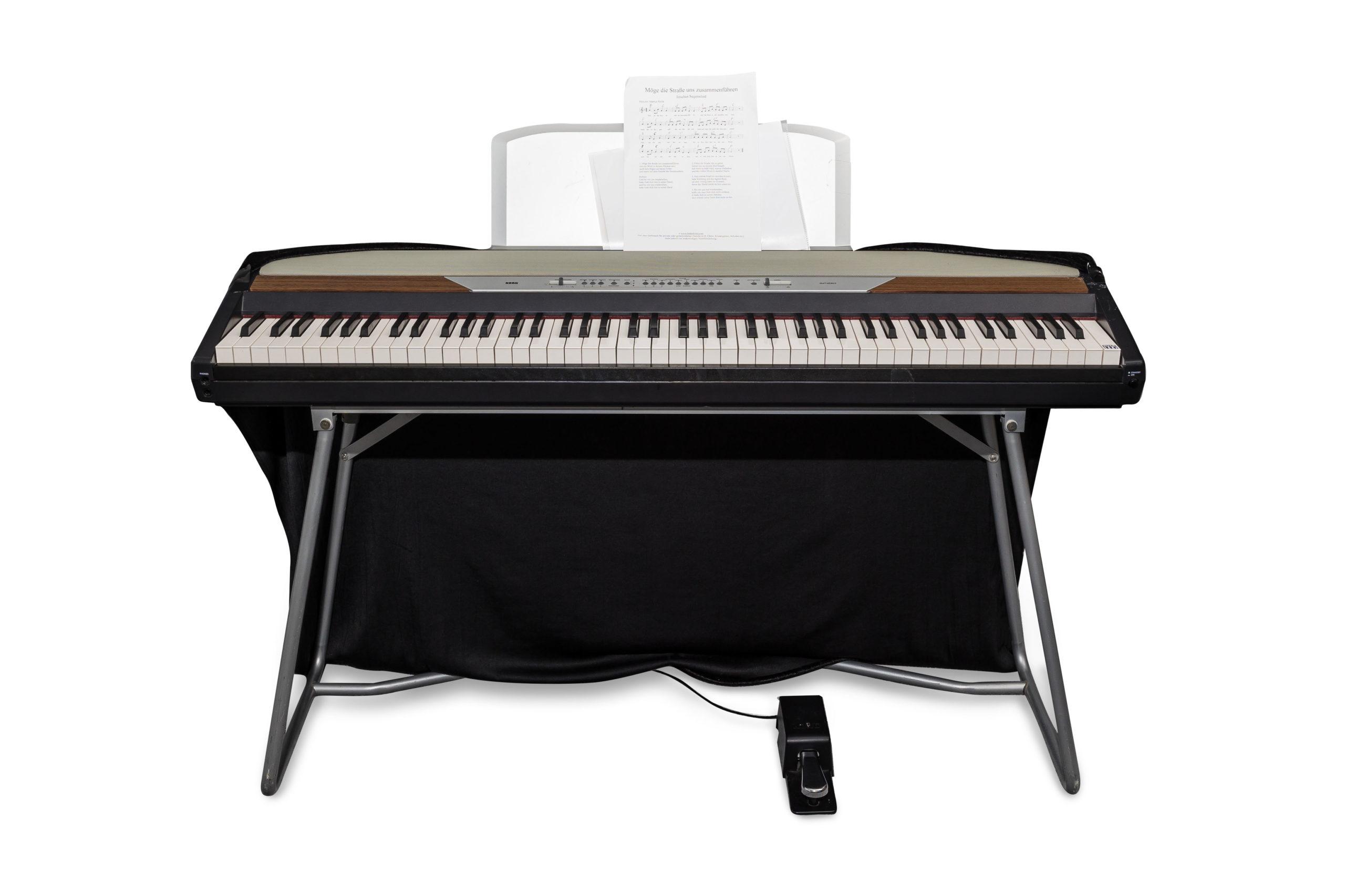 Keyboard mit Notenblatt vor weißem Hintergrund
