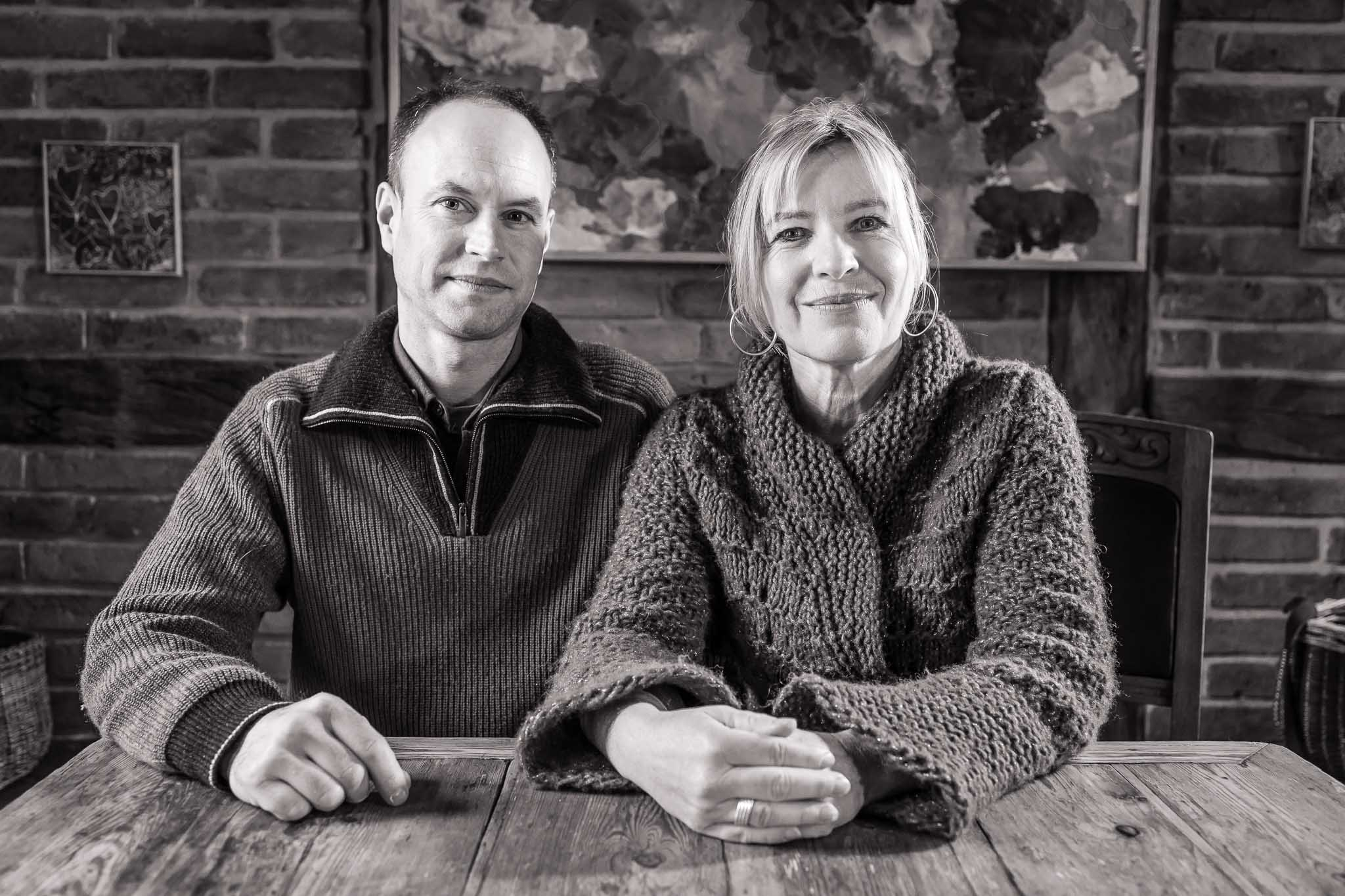 Dagmar und Lars sitzen am Küchentisch vor einem von Dagmars Gemälden